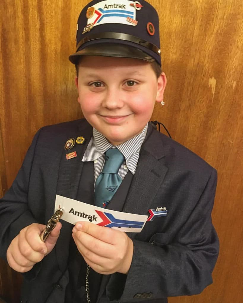 Boy dressed as an Amtrak train conductor for Halloween costume