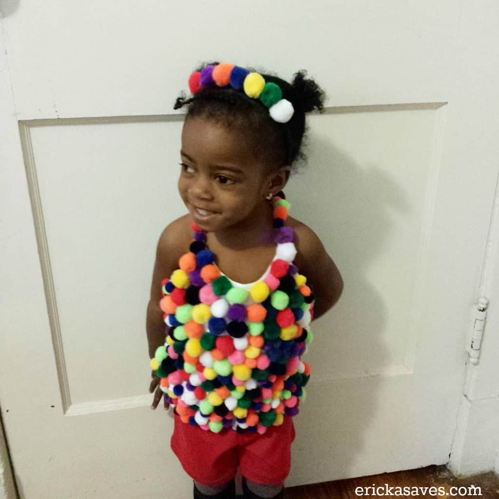 toddler girl dressed as a bubble gum machine for Halloween using pom-poms on a white tank top wearing read shorts and a headband with pompoms