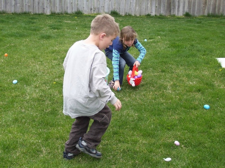 boy and girl gathering eggs in their baskets at an Easter egg hunt in backyard