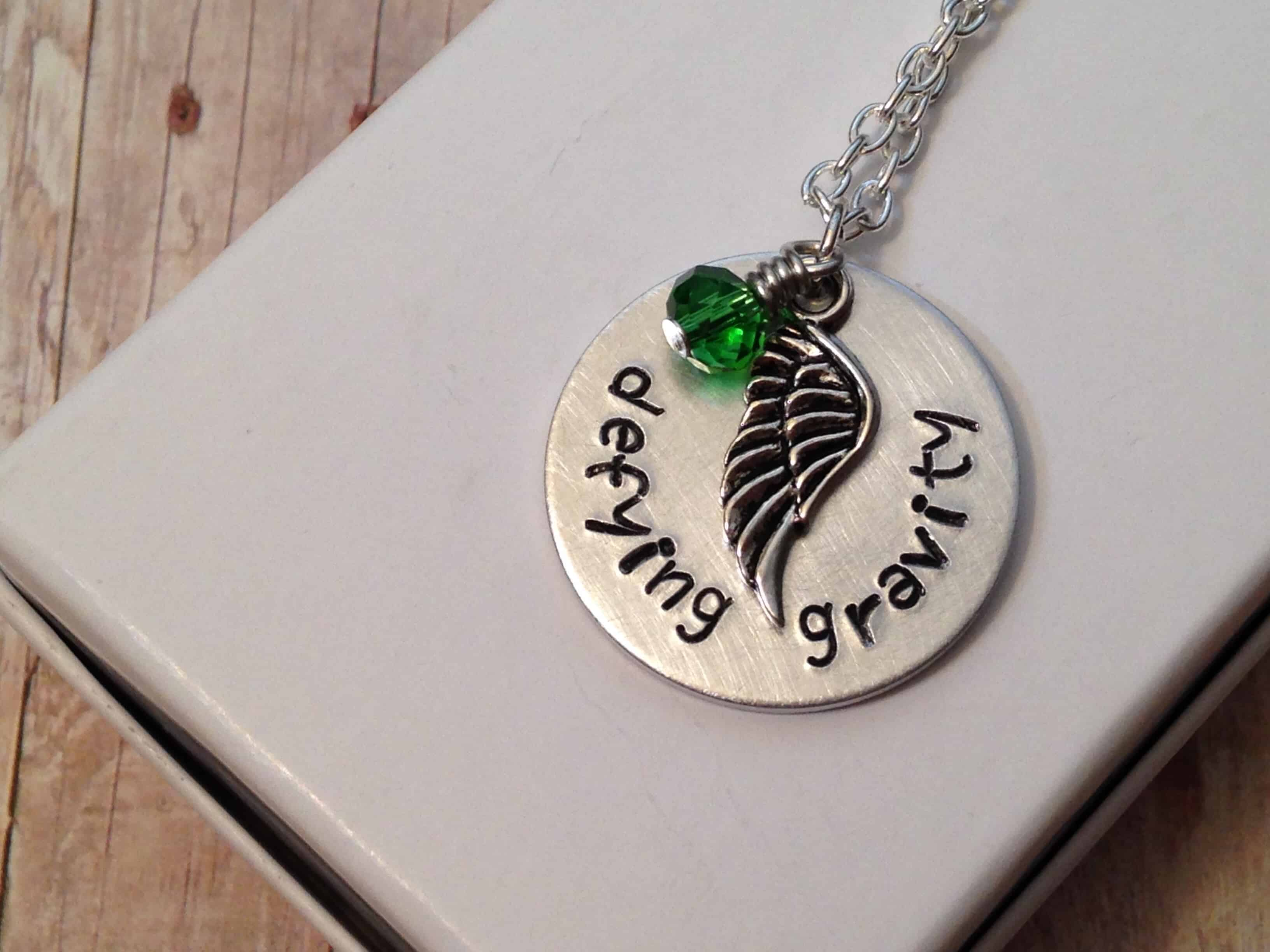 silver necklace with pendant with half wing and green jewel that says defying gravity #jewelry #etsy #handmade #handmadejewelry