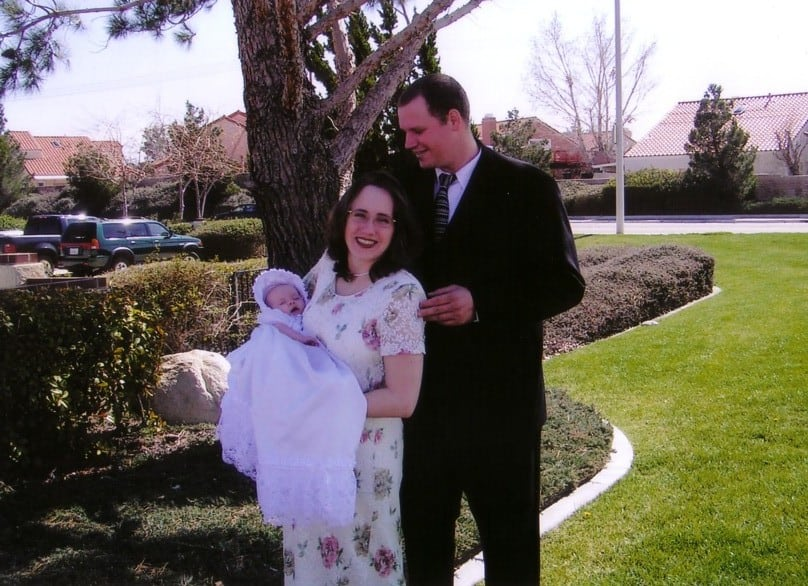 couple holding baby wearing long white blessing dress while standing by tree