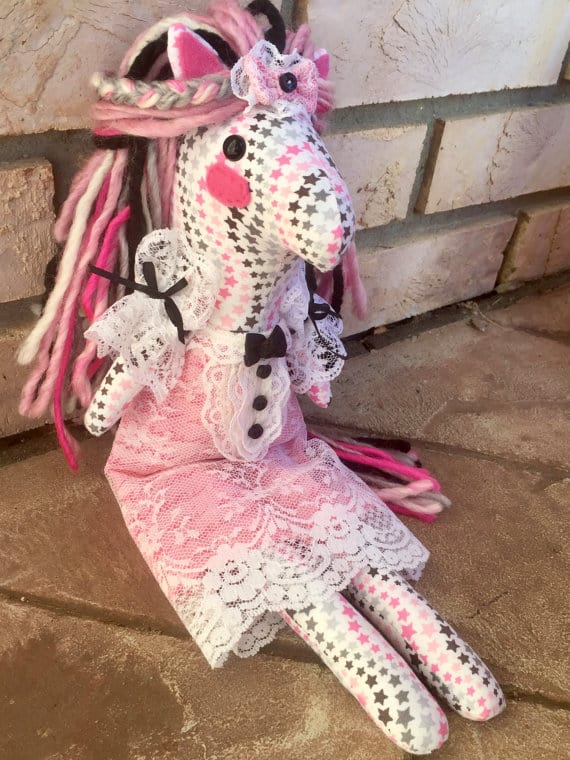 pink, white and brown pony doll with stars on fabric and lace dress