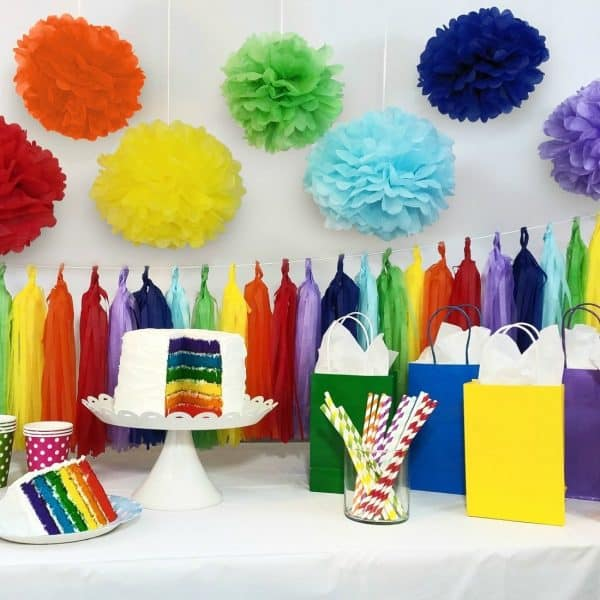 rainbow cake with rainbow party decorations and gift bags