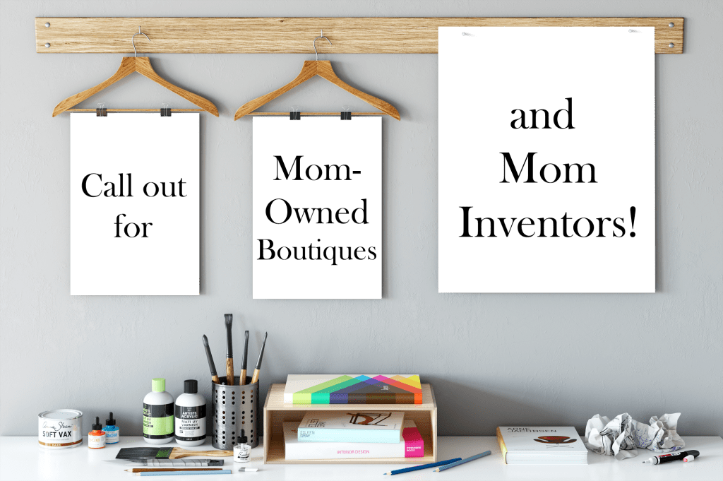 desk with art supplies and poster boards on hangers with words call out for mom-owned boutiques and mom inventors to be featured