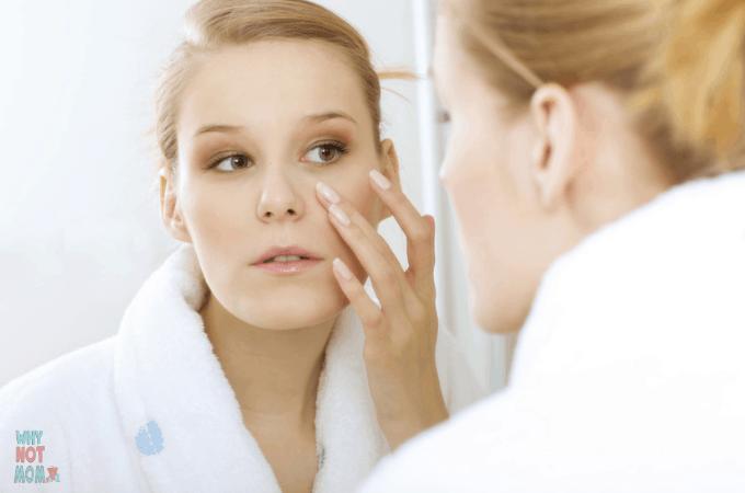 woman looking in mirror wearing bathrobe applying moisturizer face cream