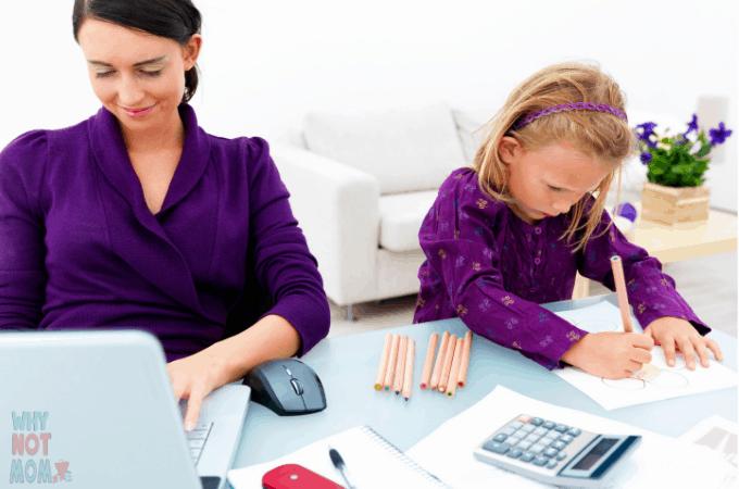 a mother working on her laptop with her daughter coloring beside her happily