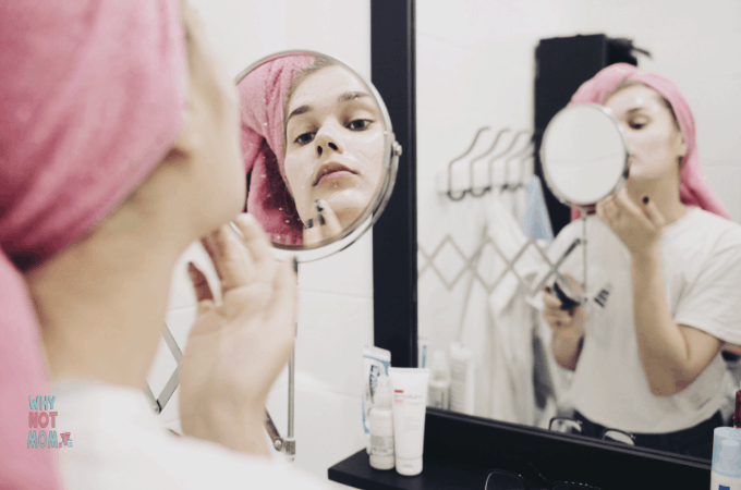 young woman with towel on head applying face mask looking in bathroom mirror