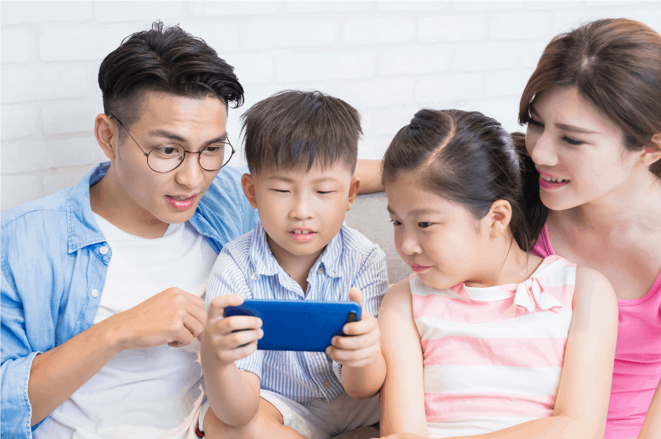 Family of Asian descent use phone to play game happily at home screen time
