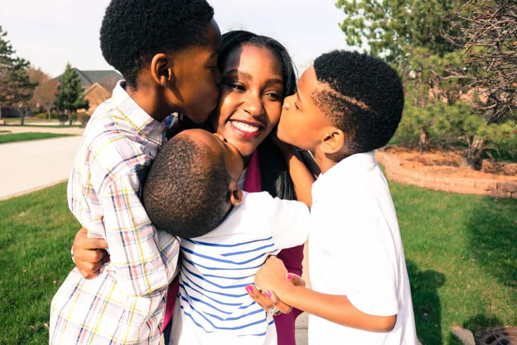 African American Mother with her 3 young sons kissing her cheek   Blog Post How a gift for a pregnant friend turned into a successful subscription service  Interview with Ericka Perry
