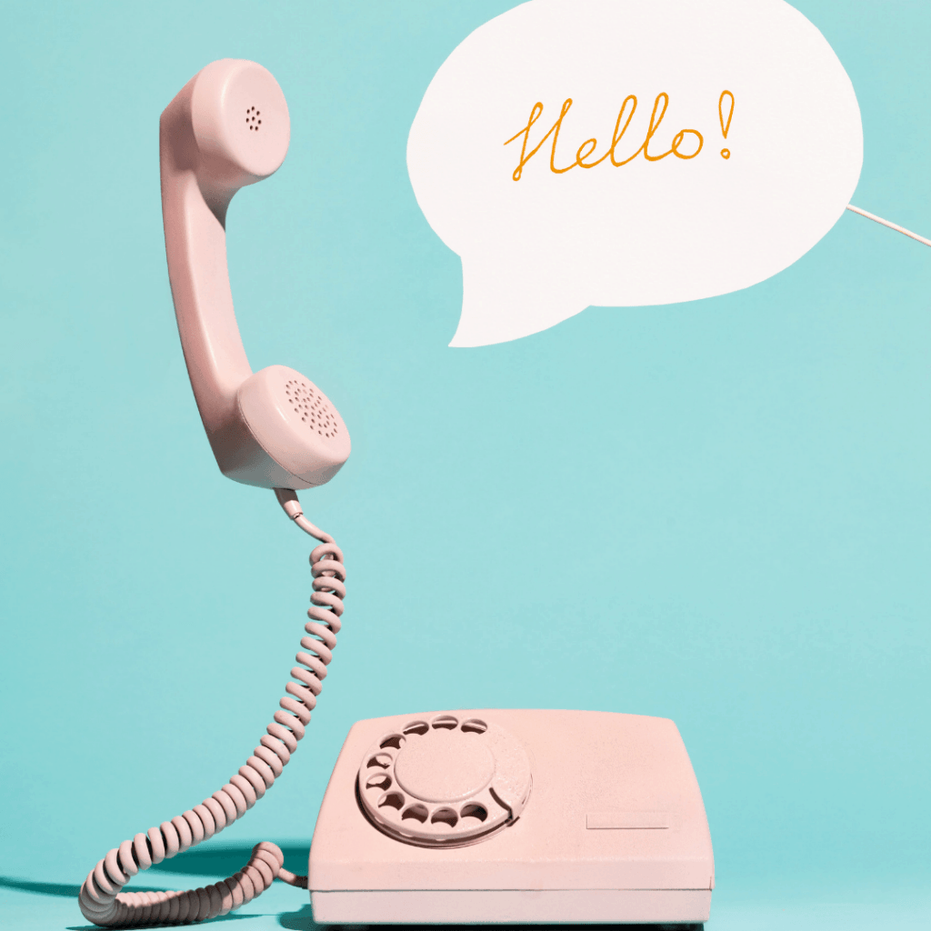 a retro corded pink phone with a word bubble that says hello
