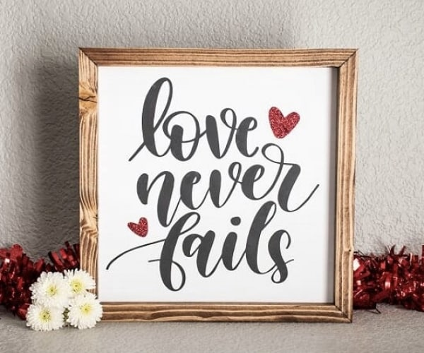 Love quote glitter sign for wall Love Never Fails quote wood sign with hand-painted quote and glittery accents. Pine wood frame dark walnut brown stained
